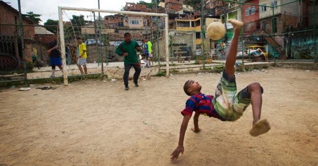 26out2013-garotos-jogam-futebol-em-campo-no-meio-da-favela-morro-dos-macacos-no-rio-de-janeiro-1386959967330_956x500